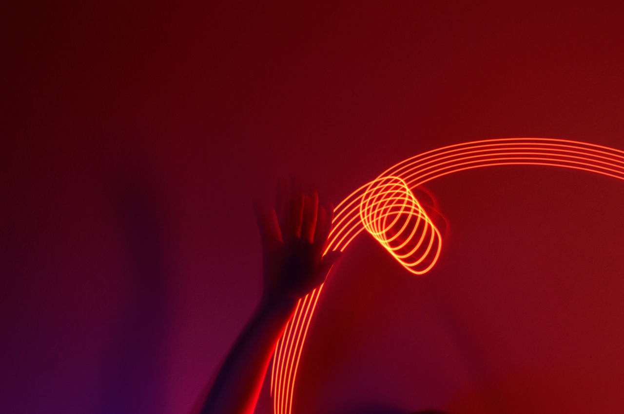 Close-up of hand against light painting