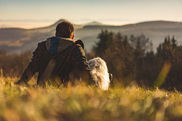 Adventure Backpack Beauty In Nature Camera - Photographic Equipment Day Dog Domestic Animals Field Grass Hiking Leisure Activity Lifestyles Mammal Men Mountain Nature One Animal One Person Outdoors Pets Real People Rear View Sitting Sunset Women