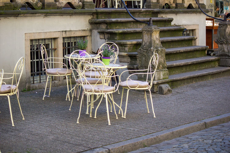 Empty chairs and tables against building in city