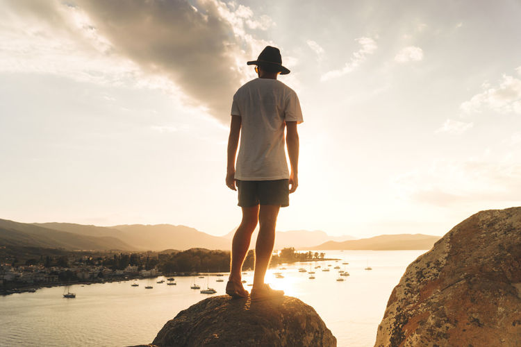 Rear view of man looking at sea while standing on rock