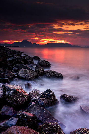 smooth water with burning sky Sea Rock Solid Sky Rock - Object Water Cloud - Sky Scenics - Nature Beauty In Nature Sunset Beach Land Nature Tranquility Tranquil Scene Horizon Over Water No People Horizon Motion Outdoors Romantic Sky