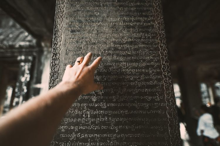 Cropped Hand Of Man Reaching Towards Text On Wall At Angkor Wat Temple