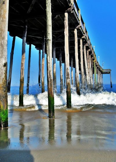 Low Angel View Of Pier Against Clear Blue Sky
