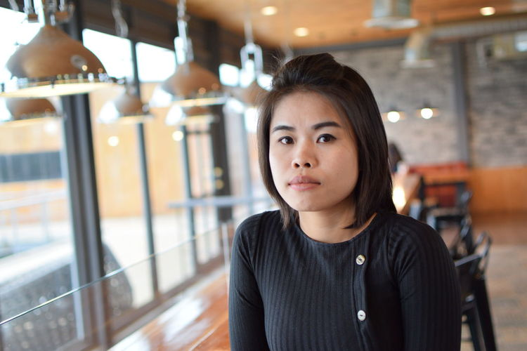 Portrait of beautiful young woman sitting in cafe