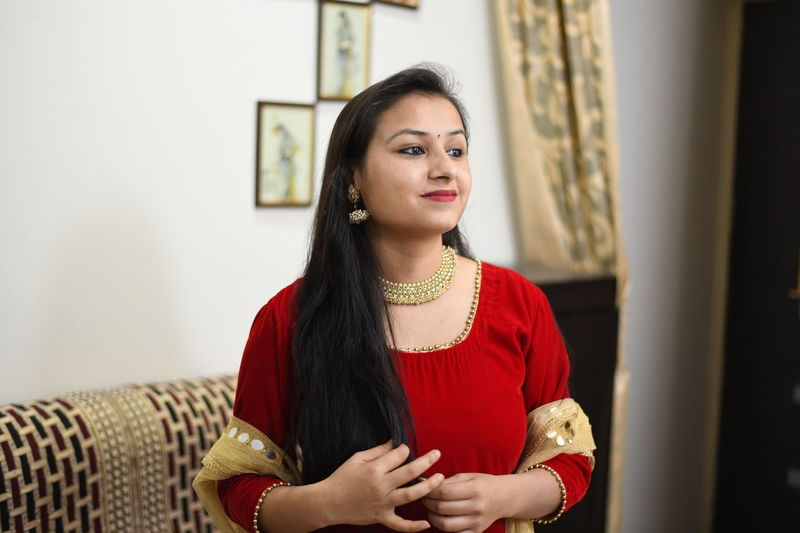 Smiling woman in traditional clothing standing at home