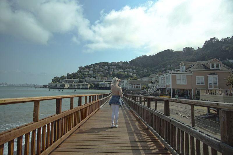 Woman on footbridge over sea against sky