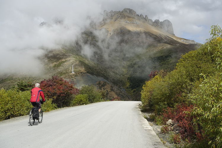 Rear view of man riding bicycle on road leading towards mountain during foggy weather