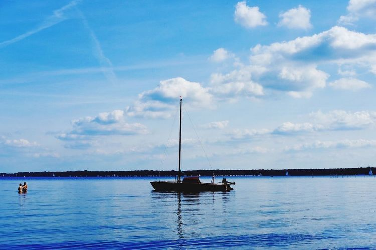 Boats sailing in calm sea against sky