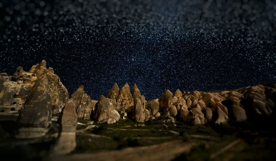 Standing rocks on landscape against starry sky