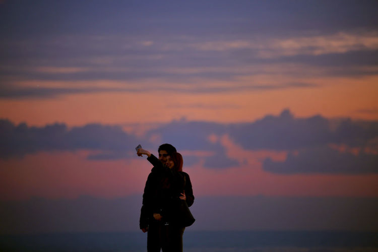 Couple taking selfie while standing against sky during sunset