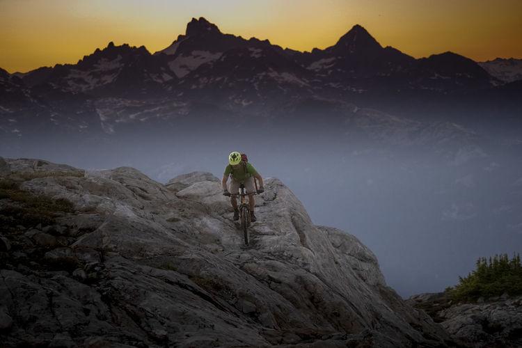 Man riding rocks on mountain against sky
