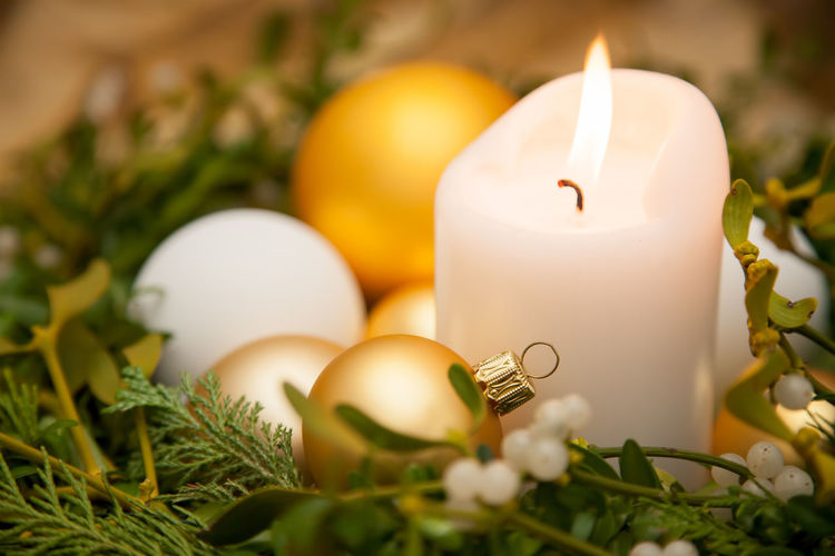 White candle in mistletoe wreath with Christmas decoration Christmas Copy Space December Golden Green Color Holiday Ornament Winter Bauble Branch Burning Candle Candlelight Christmas Card Christmas Decoration Close-up Flame Indoors  Indoors  Mistletoe No People Season  Symbol White Color Wreath