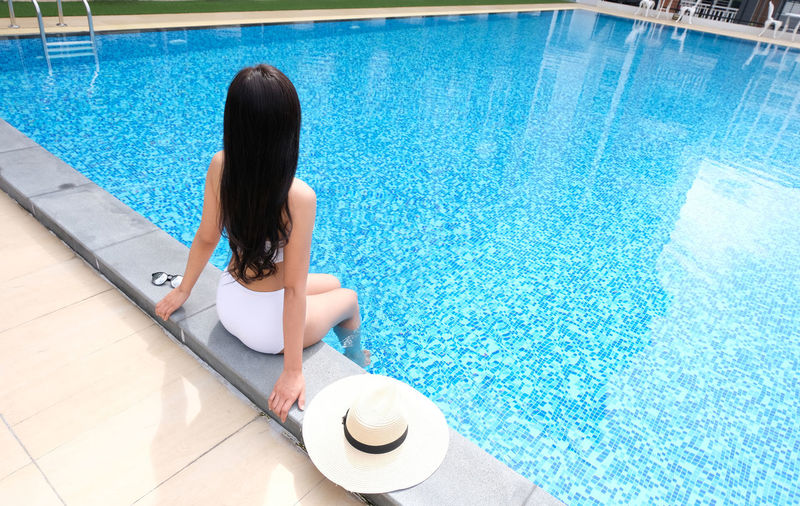 Black Hair Day Flooring Full Length Hair Hairstyle High Angle View Leisure Activity Lifestyles Nature One Person Outdoors Pool Poolside Real People Relaxation Sitting Swimming Pool Turquoise Colored Water Women
