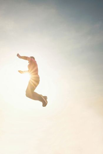 Jumping man in the sky. man jumping in the sunshine against blue sky.