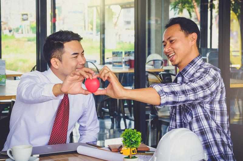 Smiling Businessmen Holding Heart Shape In Office