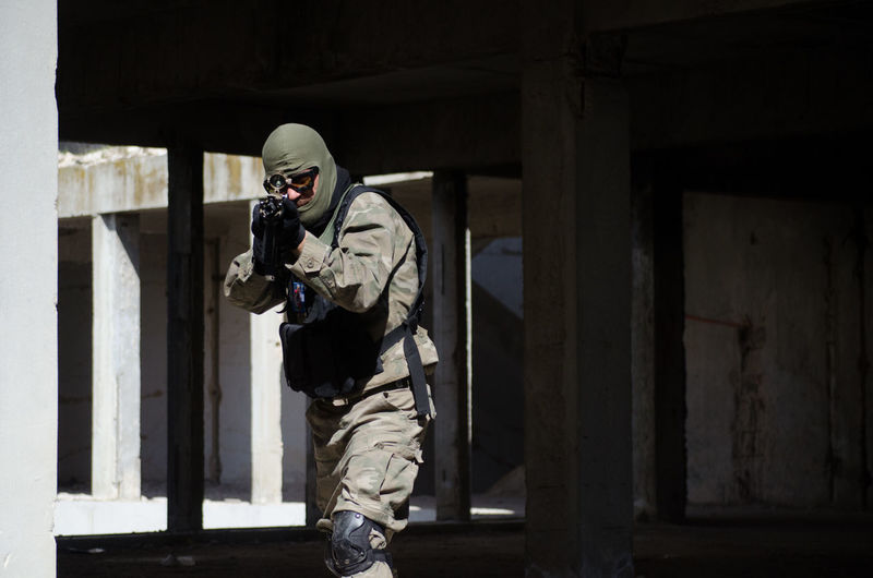 Soldier aiming with machine gun while standing in building