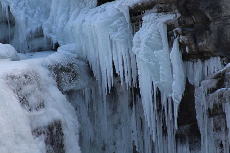 Panoramic shot of icicles on rock during winter