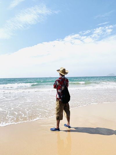 Rear view of young man with backpack standing at beach against sky