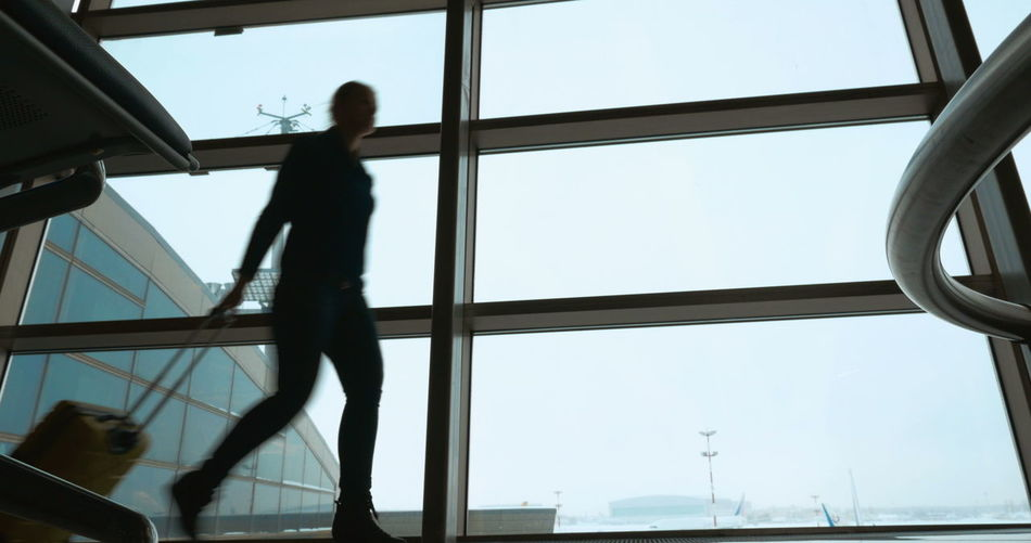 Low angle view of silhouette people at airport against sky