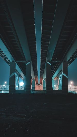Low angle view of bridge in city at night