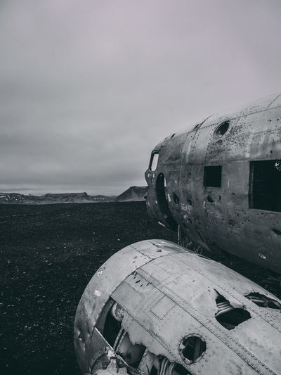 Abandoned airplane on sea shore against sky