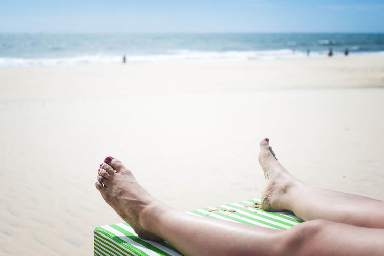 Low section of woman relaxing at beach