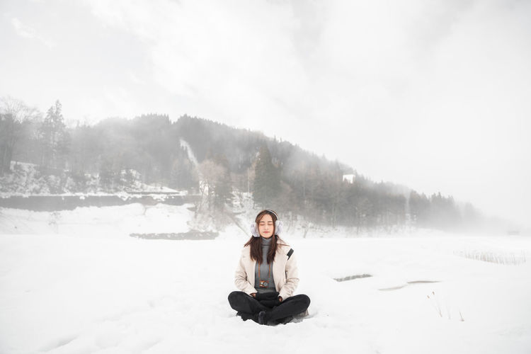 Winter Snow One Person Sitting Cold Temperature Full Length Beauty In Nature Leisure Activity Young Adult Nature Non-urban Scene Cross-legged Warm Clothing Scenics - Nature Real People Day Front View