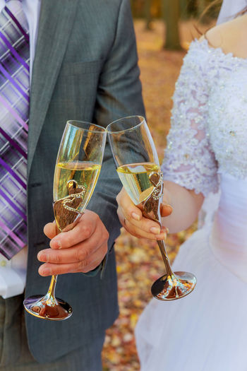Midsection Of Bride And Bridegroom Toasting Champagne Flutes