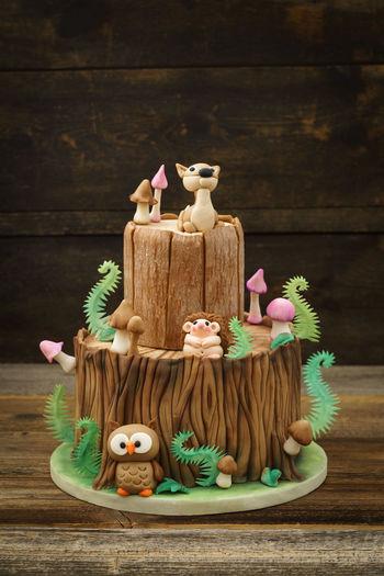 Enchanted forest woodland themed fondant cake with a hedgehog, deer, owl, tree trunk, ferns, mushrooms and leaves on wooden background Birthday Cake Fondant Cake Tree Tree Trunk WoodLand Animal Cake Celebration Character Fern Figurine  Fondant  Food Food And Drink Forest Guitar Kid Mushroom Owl Still Life Sugar Arts Sweet Food Theme