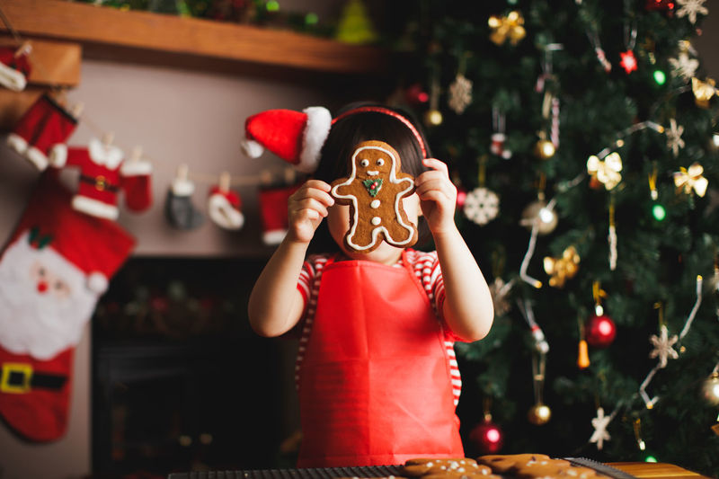 Girl with gingerbread cookie at home during christmas