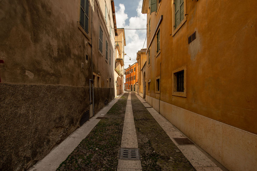A small alley in Verona Alley Architecture Building Built Structure City Day Diminishing Perspective Direction Footpath Long No People Outdoors Sky Street The Way Forward Wall - Building Feature