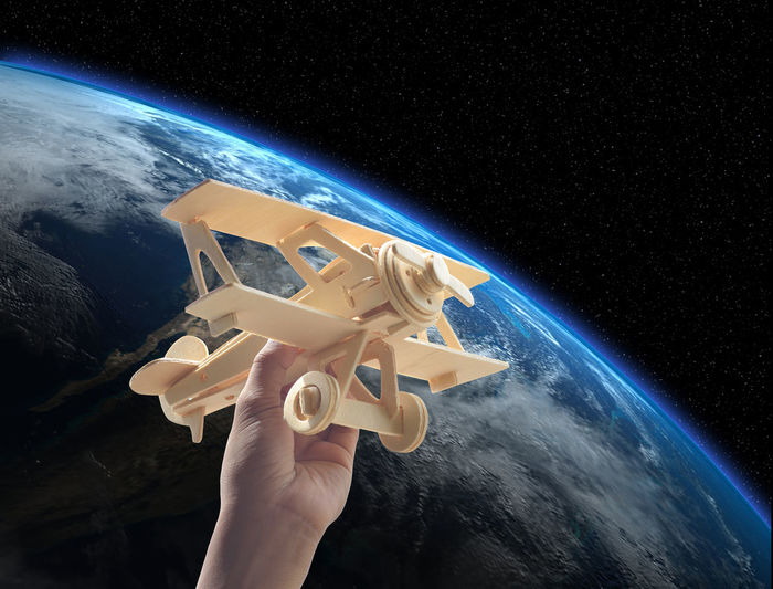 Close-up of human hand holding model airplane against planet earth in space