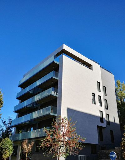 low angle view architecture building exterior built structure sky blue clear sky outdoors no people modern day illuminated tree sunsetinspain Clear sky Architecture City spanish arquitecture