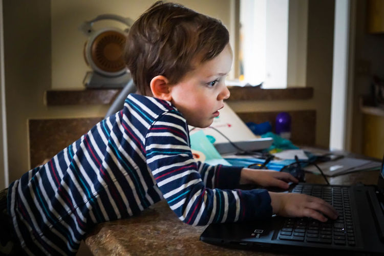 Side view of boy using laptop at home