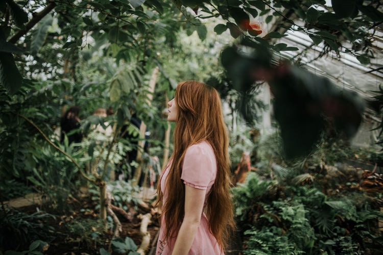 Side view of woman standing in forest
