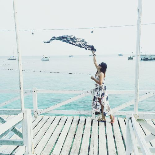 Woman holding scarf while standing on pier by sea