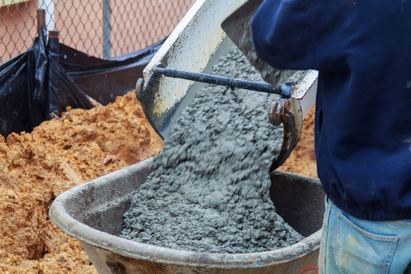 Midsection Of Worker Standing By Cement Pouring In Wheelbarrow