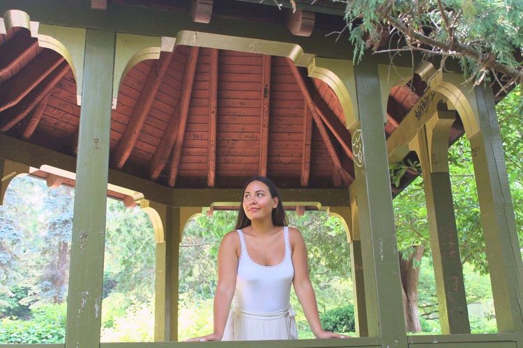 Young Woman Standing In Gazebo At Park