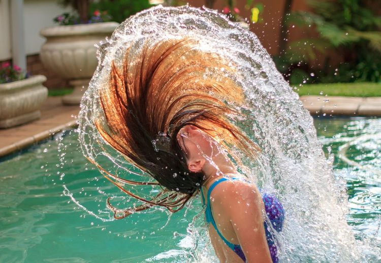 Young Woman Splashing Water In Swimming Pool