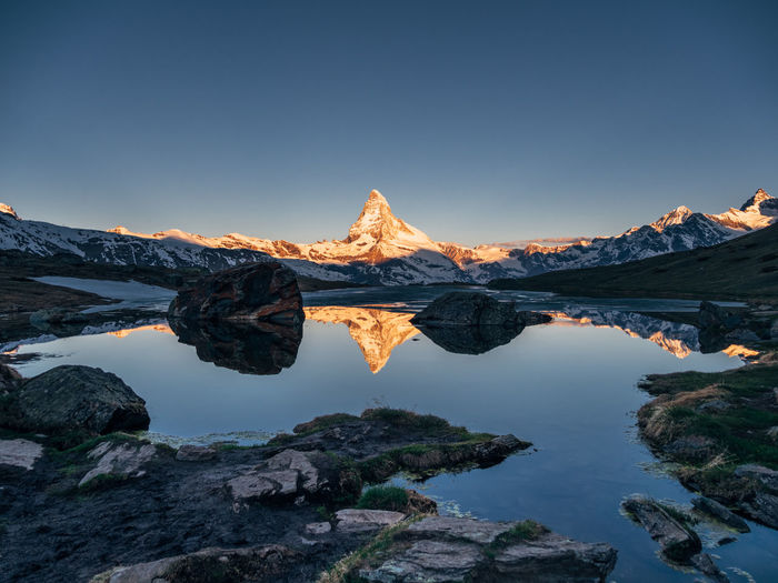 Reflection of matterhorn mountain in lake against clear sky during sunset