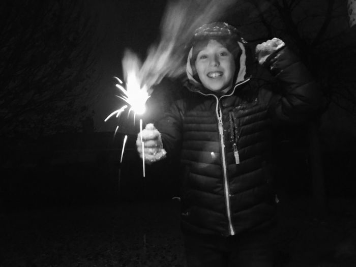 Black And White Celebrate Celebration Child Boy Night One Person Sparkler Real People Front View Childhood Burning Celebration Happiness Illuminated Looking At Camera Casual Clothing Motion Flame Holding Smiling