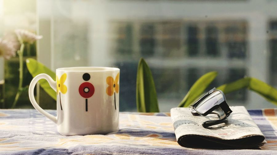 Close-up of personal accessories on table against window