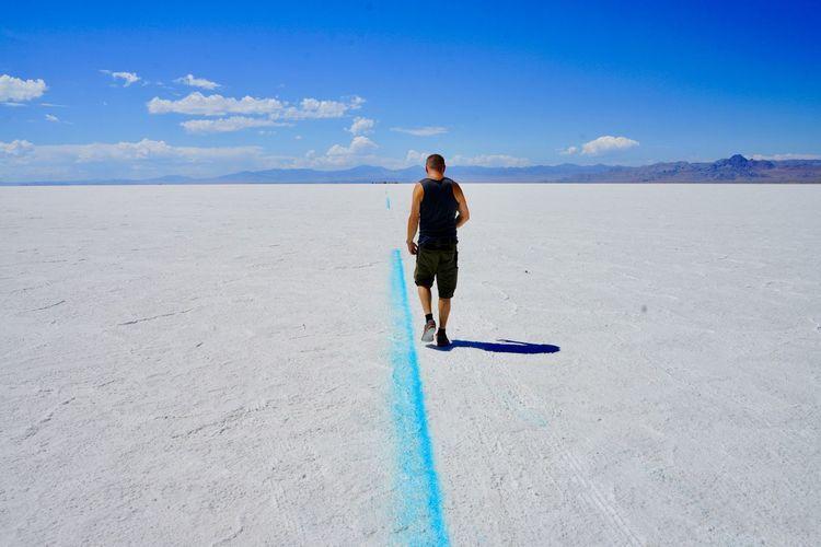 Rear view of man walking on salt flat against blue sky