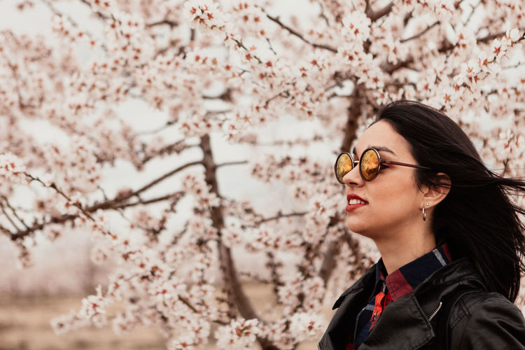 Portrait of beautiful young woman with cherry blossom