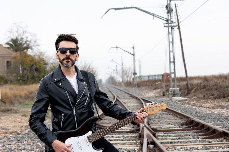 Rocker with sunglasses playing electric guitar on abandoned train tracks.