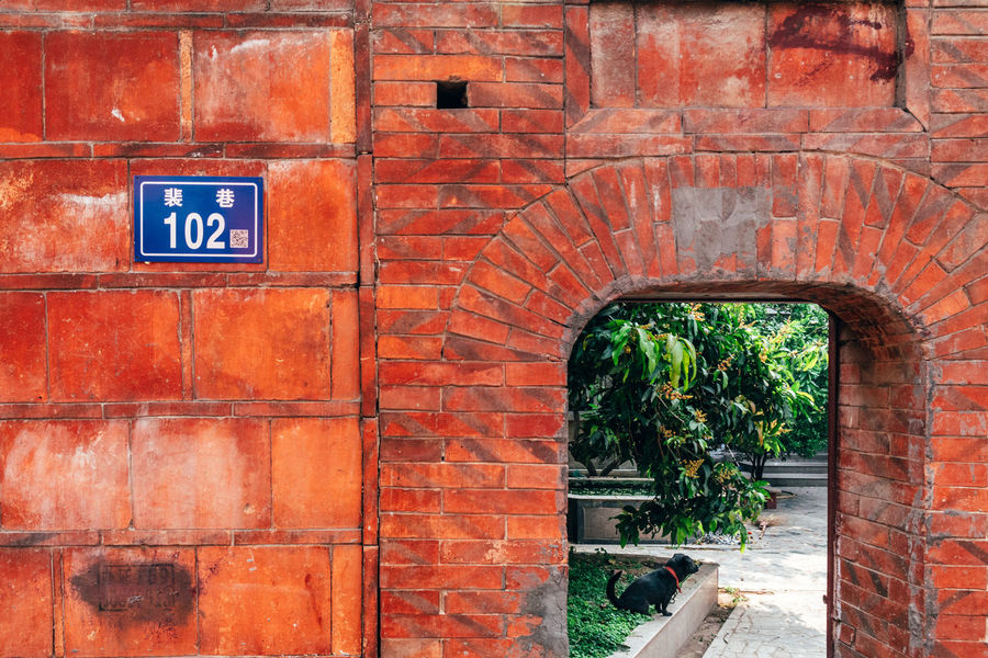 Arch Architecture Brick Brick Wall Building Building Exterior Built Structure Communication Day Historical Nature No People Old Outdoors Plant Red Sign Text Tree Wall Wall - Building Feature Western Script