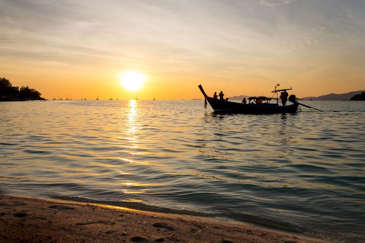 Silhouette people on longtail boat in sea during sunset