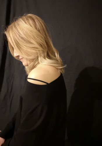 Side view of woman against black background