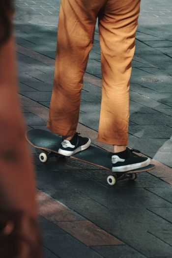 Low section of people skateboarding on footpath