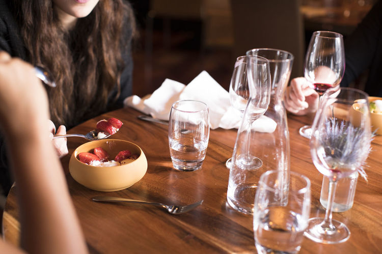 Midsection of woman with wine glasses on table finishing a meal